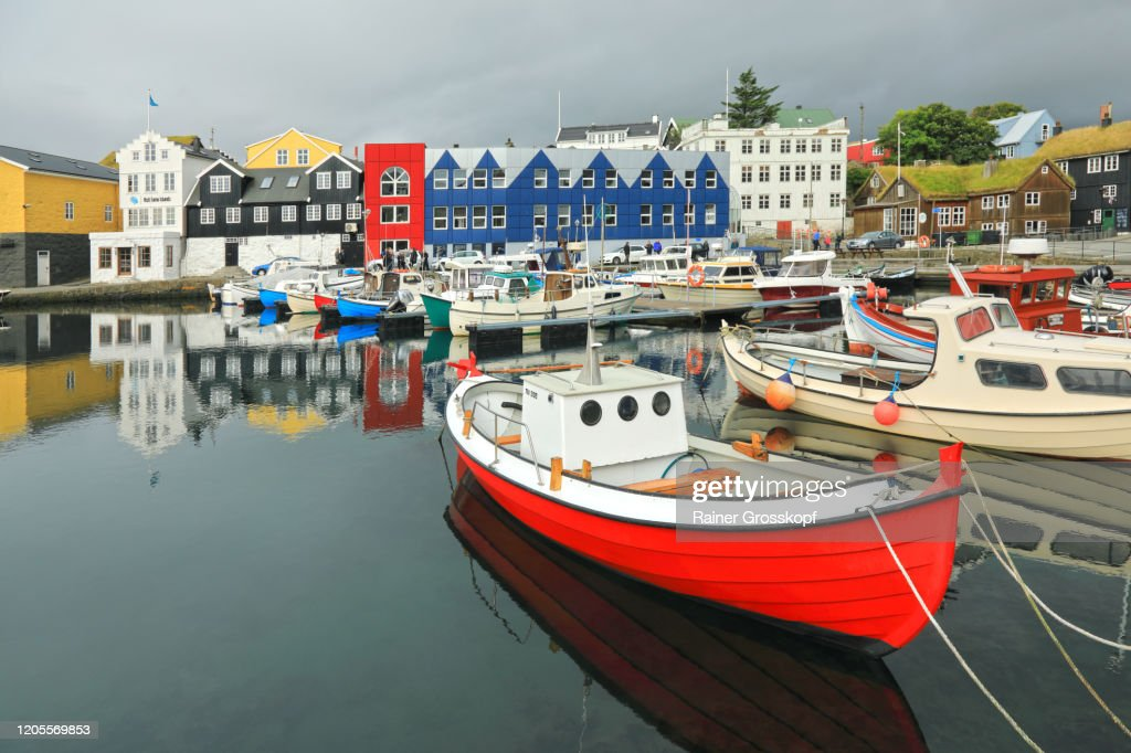 Colorful houses around a small fishing harbor with colorful boats : Stock-Foto