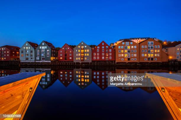 Colorful houses on stilts in Trondheim reflected in the water