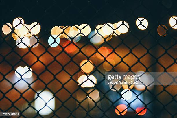 Colorful Illuminated Lights Seen From Chain Link Fence At Night