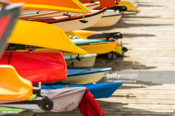 colorful kayaks and canoes by the lake on a sunny day. - istock stock pictures, royalty-free photos & images