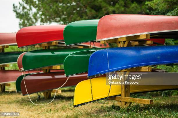 colorful kayaks and canoes by the lake on a sunny day. - istock photo stock pictures, royalty-free photos & images