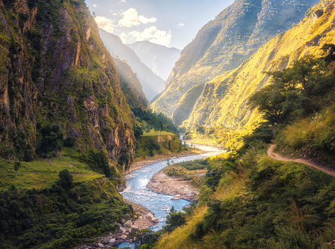 Colorful landscape with high Himalayan mountains, beautiful curving river, green forest, blue sky with clouds and yellow sunlight at sunset in summer in Nepal. Mountain valley. Travel in Himalayas 968630976