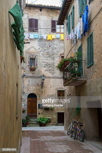 Colorful laundry is hanging outside a house to dry in Pienza, Val d'Orcia, Tuscany, Italy.