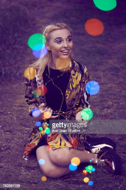 Colorful Lens Flare Of Woman Sitting On Field