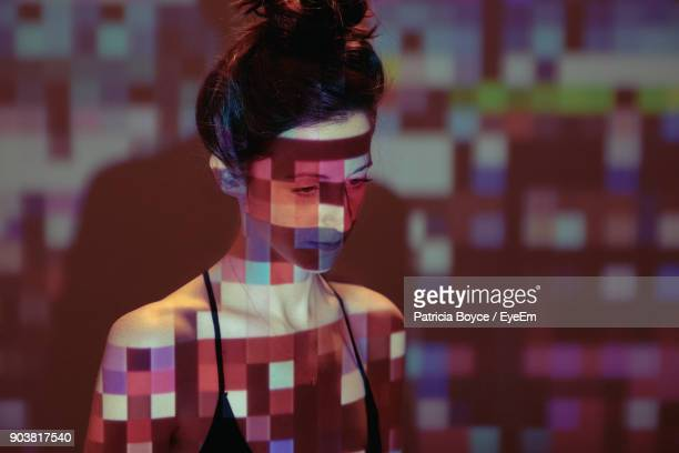 colorful light falling on mid adult woman standing against wall - projektion stock-fotos und bilder