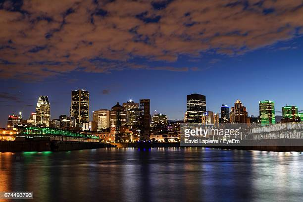 Colorful Light Reflecting On River Against Cityscape