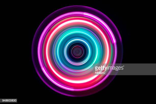 colorful light trail swirl - bewegung stock-fotos und bilder
