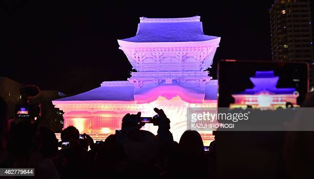Colorful lights are projected onto a large snow sculpture of the Kasuga Grand Shrine during the 66th annual Sapporo Snow Festival on February 5 2015...
