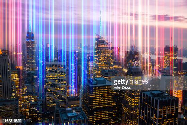 colorful lights emerging from manhattan city at dusk. - 5g foto e immagini stock