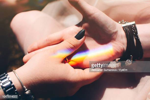 colorful lights falling on friends holding hands - 黒のネイル ストックフォトと画像