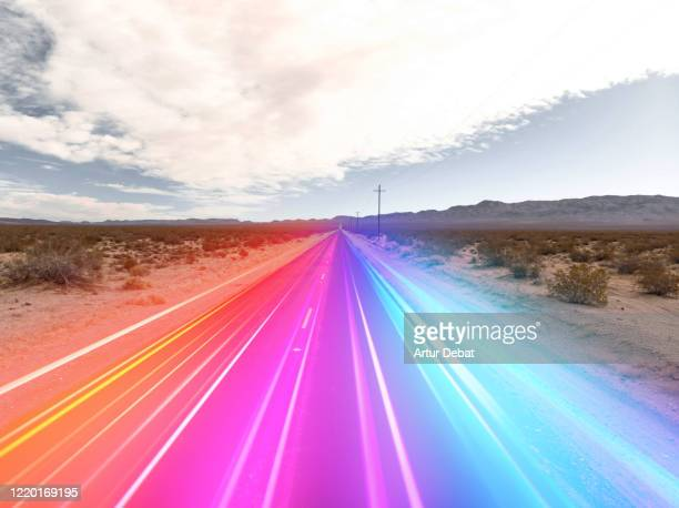 colorful lights moving fast in straight road in the california desert. - hybrid vehicle stock pictures, royalty-free photos & images