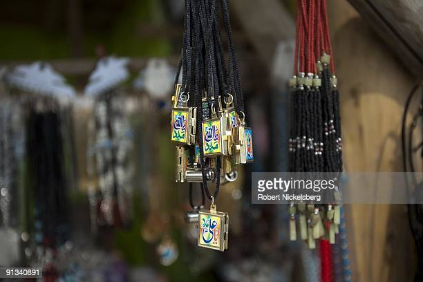 Colorful lockets with islamic inscriptions hang in a shopkeepers stall outside the ZiaratiSakhi shrine in Kabul Afghanistan March 2 2009 The shrine...
