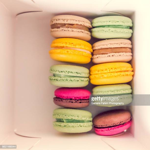 colorful macaroons in box - samere fahim stock photos and pictures