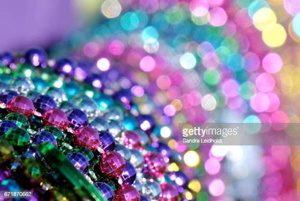 colorful mardi gras bead bokeh - mardi gras flashing stock photos and pictures