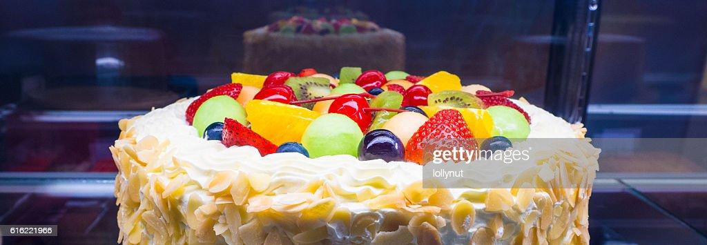 Colorful mixed fruit fresh cream cake in refrigerator showcase : Photo