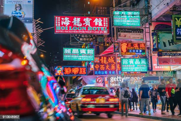 Colorful neon night street road in Hongkong with taxi