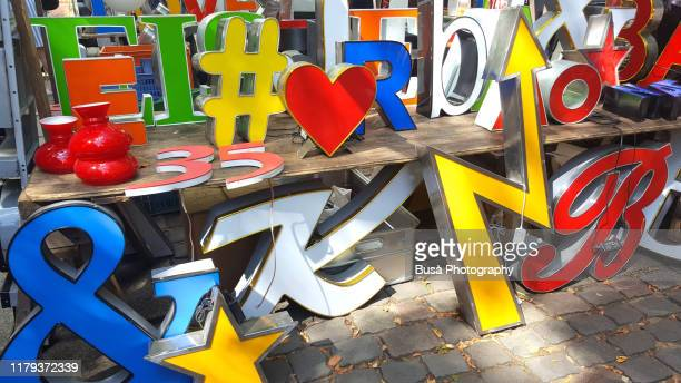 colorful neon signs for sale in a flea market - advertisement stock pictures, royalty-free photos & images