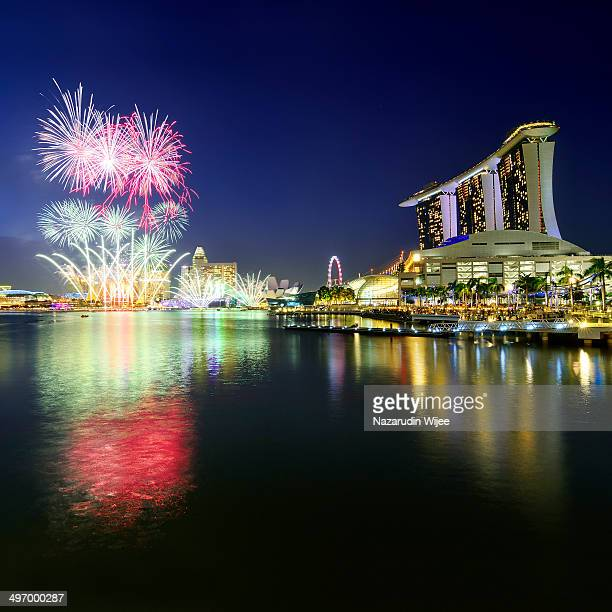 CONTENT] Colorful night city light with fireworks view from Raffles Quay towards Marina Bay Sand and Singapore Flyer during National Day Parade...