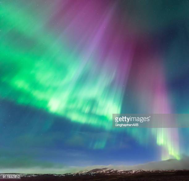 colorful northern light aurora borealis in iceland night sky with mountain range below - poolklimaat stockfoto's en -beelden