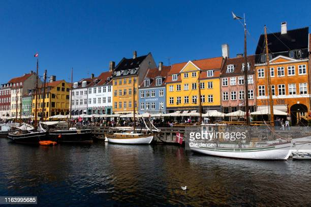 """Colorful old houses in the historic Nyhavn on August 25, 2019 in Copenhagen, Denmark. Nyhavn means """"New Harbour"""" but it is actually the old harbor..."""