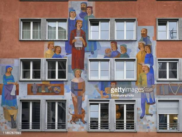 colorful painted human figures on a building facade,lucerne. - emreturanphoto stock pictures, royalty-free photos & images