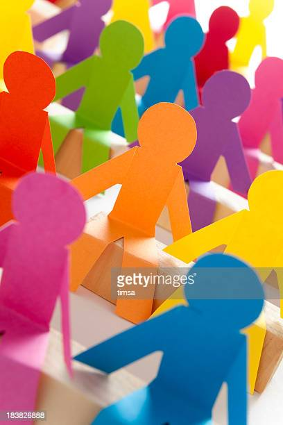 Colorful paper cut-outs of a seated group of peers