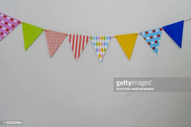 colorful paper flags hanging on grey background - bunting stock pictures, royalty-free photos & images