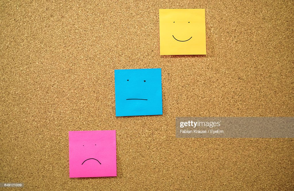 Colorful Papers With Anthropomorphic Faces Stuck On Wall : Stock Photo