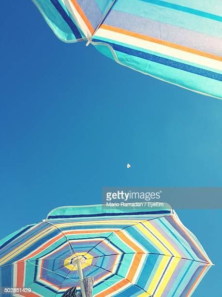 Colorful parasols against clear blue sky