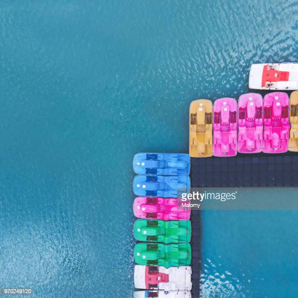 colorful pedal boats in blue water. directly above, aerial view. drone view. - pedal boat stock pictures, royalty-free photos & images