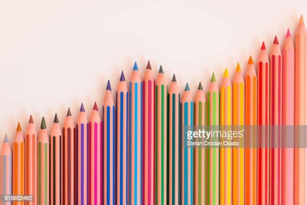 colorful pencils arranged on desk - 玉虫色 ストックフォトと画像