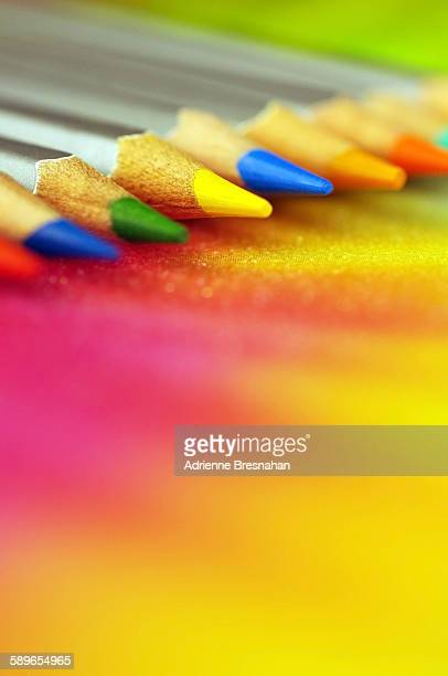 Colorful pencils on top of colorful paper