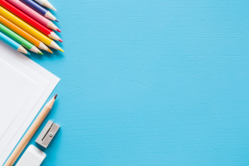 Colorful pencils, white papers and metal pencil sharpener. Empty place for text or drawing on the blue background. Childhood creative art concept. Flat lay. 925244914