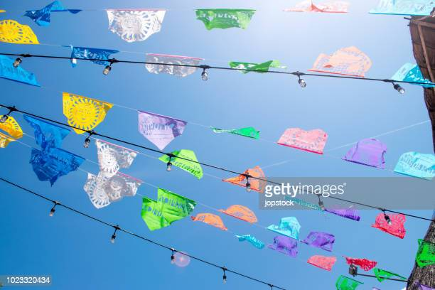 colorful pennant flags for party decoration against sky - mexican fiesta stock pictures, royalty-free photos & images