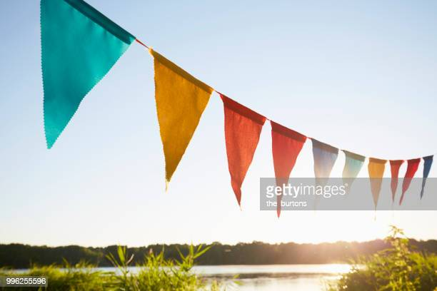 colorful pennant flags for party decoration at lake against sky - insígnia - fotografias e filmes do acervo