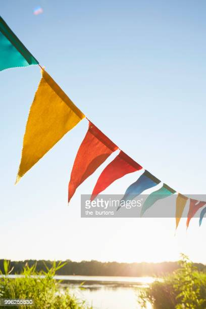 colorful pennant flags for party decoration at lake against sky - hanging stock pictures, royalty-free photos & images