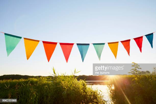 colorful pennant flags for party decoration at lake against sky - flag stock pictures, royalty-free photos & images
