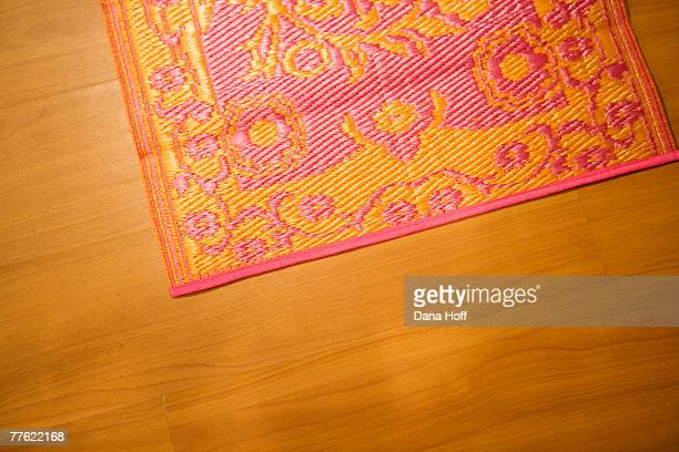 A colorful pink and orange floral area rug on a wood floor