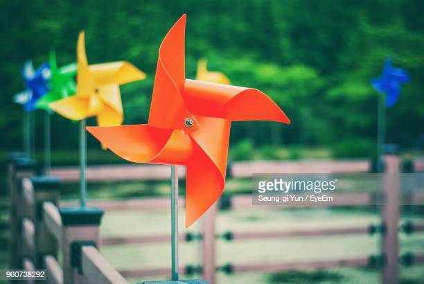 colorful pinwheels toys on railing - paper windmill stock photos and pictures