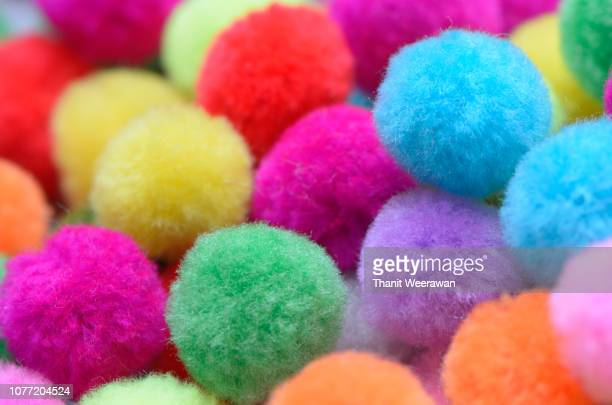 a colorful  pom pom background. - hairy balls stock photos and pictures