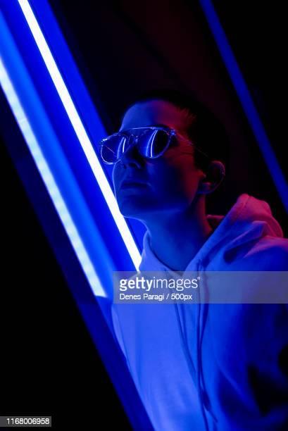 colorful portrait of a short haired woman in a neon light - generation z stockfoto's en -beelden