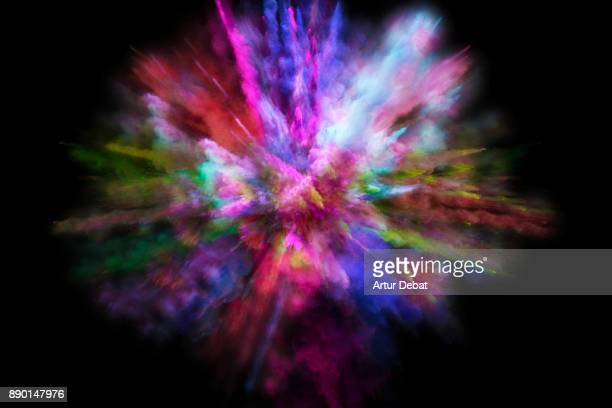 colorful powder explosion in all directions in a nice composition with vivid colors and black background. - bontgekleurd stockfoto's en -beelden