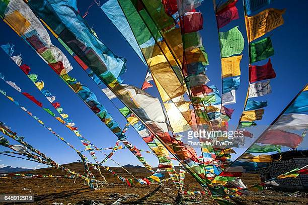 Colorful Prayer Flags Over Landscape Against Sky