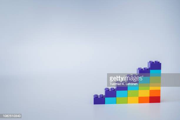 colorful rainbow colored ascending stacks made of toy building bricks on gray background. copy space. - bar graph stock pictures, royalty-free photos & images