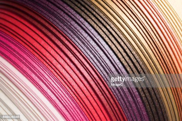 colorful red shiny texture paper stripes - cosmetics stock photos and pictures