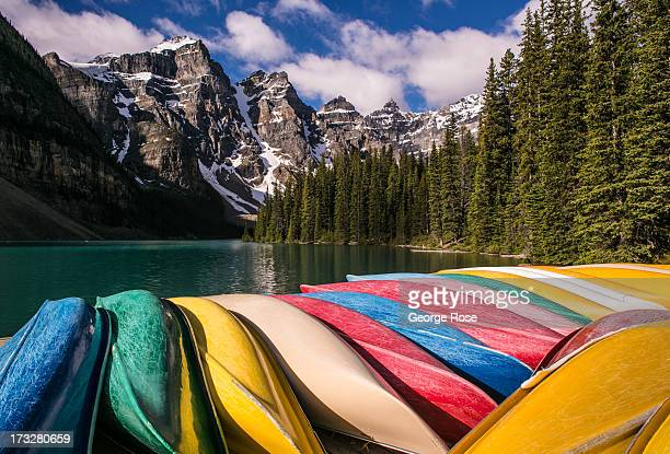 Colorful rental canoes are stacked on a pier with a view of surrounding snowcapped mountains on June 27 2013 at Moraine Lake Alberta Canada Major...