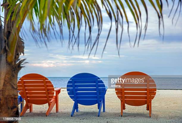 Colorful round wooden beach chairs at holiday resort on Caye Caulker / Cayo Caulker, coral island off the coast of Belize in the Caribbean Sea .