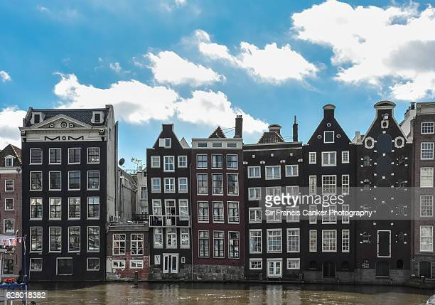 Colorful row of houses by the canal in typical Dutch style in Amsterdam, Netherlands
