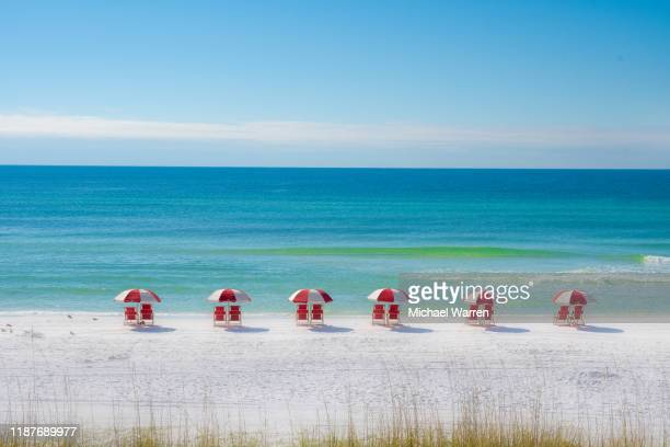 colorful row of red chairs on the beach - destin beach stock pictures, royalty-free photos & images