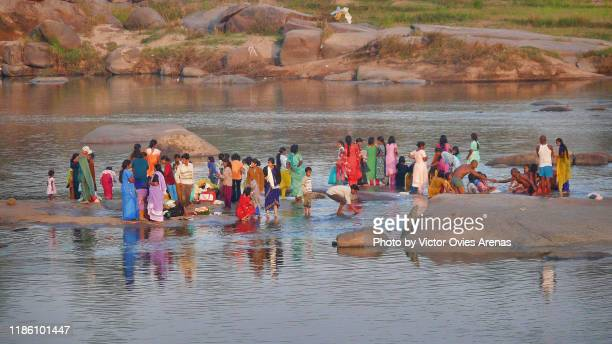 colorful scene. local people during morning ablutions in the tungabhadra river in hampi, karnataka, india - victor ovies fotografías e imágenes de stock